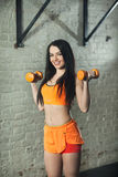 Beautiful girl with dumbbells. In sportswear on training Stock Images