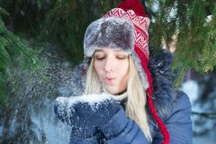 Beautiful girl in ear-flap hat blows out snow. Near green fir tree outdoor in winter day Stock Photos