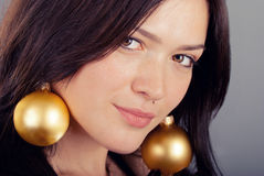 Beautiful girl with earrings of Christmas toys Stock Images