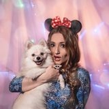 Beautiful girl with ears on her head and a dog with white Pomeranian stock photo