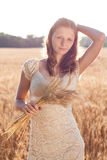 Beautiful girl with ears of wheat in the hands at sunset Royalty Free Stock Photography
