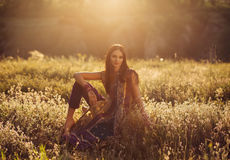 Beautiful girl eastern. Appearance sits among flower fields at sunset, fashionable toning, creative color Stock Photos
