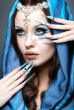 Beautiful girl in eastern Arabic image with long nails and bright blue make-up. Picture taken in the studio on a gray background Royalty Free Stock Images