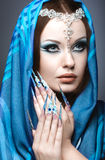 Beautiful girl in eastern Arabic image with long nails and bright blue make-up. Stock Images