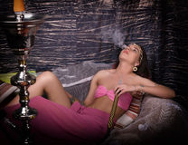 Beautiful girl in eastern dress smokes a hookah Stock Photography