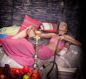 Beautiful girl in eastern dress smokes a hookah Stock Images