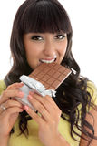 Beautiful girl eating decadent chocolate bar. Closeup of a beautiful lively happy young woman eating from a chocolate block Royalty Free Stock Images