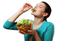 Beautiful girl eating a delicious salad of fresh vegetables. Royalty Free Stock Photos