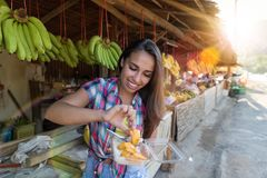 Beautiful Girl Eating Exotic Fruits On Traditional Street Market Happy Smiling Attractive Female Tourist In Asian Bazaar Royalty Free Stock Images