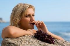 Beautiful girl eating grapes stock image