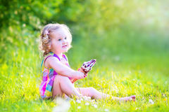 Beautiful girl eating ice cream in the sunny garden Stock Images