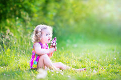 Beautiful girl eating ice cream in sunny garden Stock Photography