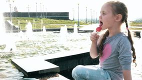 Beautiful girl eating lollipop near a fountain on a bright day. 4k stock footage