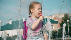 Beautiful girl eating lollipop near a fountain on a bright day stock video footage