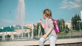 Beautiful girl eating lollipop near a fountain on a bright day stock video