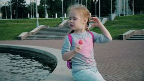 Beautiful girl eating lollipop near a fountain on a bright day. 4k stock video