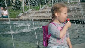 Beautiful girl eating lollipop near a fountain on a bright day. 4k stock video footage