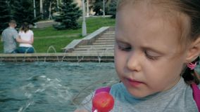 Beautiful girl eating lollipop near a fountain on a bright day stock footage