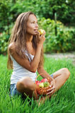 Beautiful girl eating pear on the green grass. In the garden Stock Photo