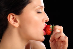 Beautiful girl eating red tasty strawberry fruit Royalty Free Stock Photography