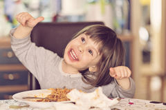 Beautiful girl eating spaghetti making faces Stock Photos