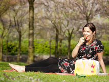 Beautiful girl eating a strawberry during a picnic. In the spring stock photography