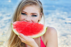 Beautiful girl is eating watermelon on the beach Stock Photos