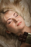 Beautiful girl eats chocolate. Picture of a Beautiful girl eating chocolate Stock Photography