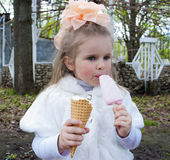 The beautiful girl eats ice-cream. Frozen favourite delicacy for children Stock Image