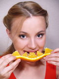 Beautiful girl eats an orange segment Royalty Free Stock Image