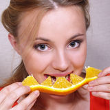 Beautiful girl eats an orange segment Stock Photos