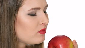 Beautiful girl eats red apple on white background stock video