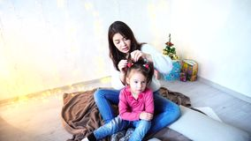 Communication of older female sister with youngest girl sitting on floor in room on background of wall with garland and stock footage