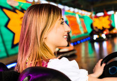 Beautiful girl in an electric bumper car in Stock Photo