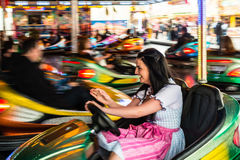 Beautiful girl in an electric bumper car at. Beautiful girl in an electric bumper car in amusement park in typical German Dirndl dress with bright colours and Royalty Free Stock Photo