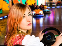 Beautiful girl in an electric bumper car at Royalty Free Stock Photography