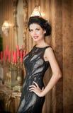 Beautiful girl in elegant black dress posing in vintage scene. Young beautiful woman wearing luxurious dress. Seductive brunette. Woman in luxury manor Stock Photography