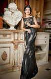 Beautiful girl in elegant black dress posing in vintage scene. Young beautiful woman wearing luxurious dress. Seductive brunette. Woman in luxury manor Stock Photos