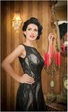 Beautiful girl in elegant black dress posing in vintage scene. Young beautiful woman wearing luxurious dress. Seductive brunette. Woman in luxury manor Stock Photo