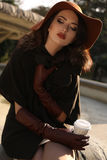 Beautiful girl in elegant coat and hat drinking coffee at park Stock Photos