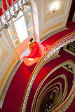 Beautiful girl in elegant dress coming down the staircase Royalty Free Stock Photo