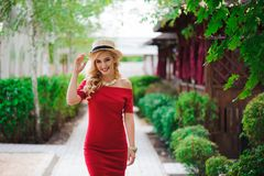 Beautiful girl in elegant dress and hat and charming smile posing for the photographer in the park. royalty free stock image