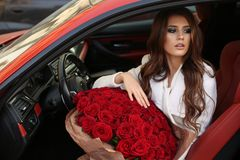 Beautiful girl in elegant dress posing in luxurious car with bo. Fashion photo of beautiful girl with dark hair in elegant dress posing in luxurious car with stock photos