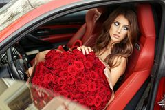Beautiful girl in elegant dress posing in luxurious car with bo. Fashion photo of beautiful girl with dark hair in elegant dress posing in luxurious car with royalty free stock photography