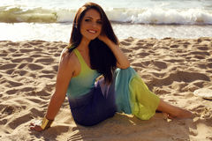 Beautiful girl in elegant dress relaxing on summer beach Royalty Free Stock Image