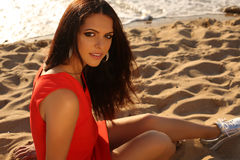 Beautiful girl in elegant red dress relaxing on summer beach Stock Photos