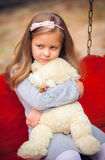 Beautiful girl embraces an amusing bear Stock Images