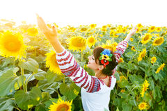 Beautiful girl in embrodery rise hands up on a sunflower plant Stock Photos