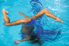 Beautiful girl is engaged in synchronized swimming. In pool Royalty Free Stock Images