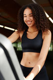 Beautiful girl is engaged on a treadmill and charmingly smiles. Portrait of charming woman changing treadmill screen options while she laughing feeling so happy Stock Image